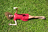 Teenage girl lying on grass holding paper airplane
