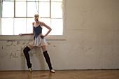 Ballet dancer warming up by window