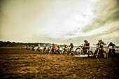 Group of boys on motorcycles at motocross start line