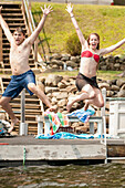 Young couple jumping into lake