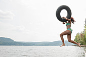 Young woman jumping into lake holding inflatable ring