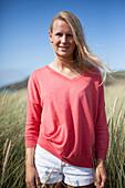 Portrait of blonde woman wearing pink sweater in marram grass, Wales, UK