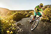 Young man mountain biking on dirt track, Monterey, California, USA