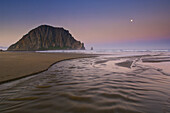 Moonset at dawn over Little Morro Creek and Morro Rock, Morro Strand State Beach, Morro Bay, California.