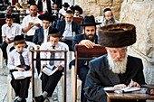 Orthodox jewish people praying at a synagogue by the western wall wall (Wailing wall) in the old city, Jerusalem, Israel.