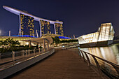 A walkway in marina Bay. On the left hand side the three tall towers of mrina Bay Sands Hotel. On the right side the Loius Vuitton Island Maison, a luxury concept store. Singapore.