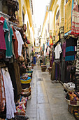 Shopping boutiques along an alleyway at an Arab souk in Granada, Spain, Europe.