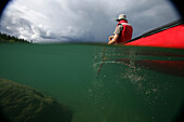 Vignetted Underwater Image Of A Man Canoeing On Kusawa Lake, Yukon