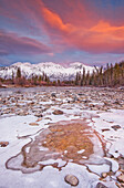 The Wheaton River In Early Winter With The Clouds Lit By Sunset Light. Snow Covered Mountains Seen In The Distance. Located Outside Of Whitehorse, Yukon. Rocks Surrounded By Ice In Foreground.