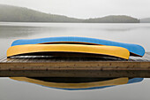 Blue And Yellow Canoes On Cottage Dock On A Misty Morning, Algonquin Park, Ontario