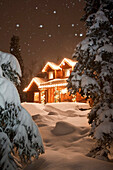Log Home Decorated With Christmas Lights With Snow Falling Overhead, Anchorage, Southcentral Alaska