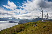 Hikers Enjoying A Sunny Afternoon Walk Near The Wind Turbines, Part Of The Pillar Mountain Wind Project, Operated And Owned By The Kodiak Electric Association, Pillar Mountain, Kodiak Island, Southwest Alaska, Summer