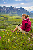 Woman Writes In Her Journal While Sitting Amid Wildflowers On The Tundra Near Eielson Visitor Center Denali Np Alaska