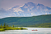 Three People In One Canoe On Wonder Lake With Mt. Mckinley In Background In Denali National Park, Alaska During Summer