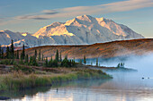 Morning Fog Over The Calm Waters Of Wonder Lake At Sunrise, Mt Mckinley Looms In The Distance, Denali National Park And Preserve, Alaska, Fall