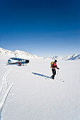 A Backcountry Skier And Snowboarder Get Dropped Off By A Cessna 170 Ski Plane On Eagle Glacier In The Chugach Mountains On A Sunny Day, Southcentral Alaska, Winter/N