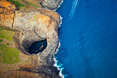 'Aerial view of the rugged coastline and tide pool in a hole along an hawaiian island; Hawaii, United States of America'