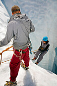 Woman Being Belayed Into Moulin On The Root Glacier Near Kennicott Southcentral Alaska Summer