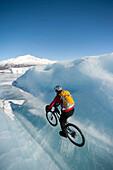 Woman Mountain Biking On The Ice Of The Knik Glacier, Chugach Mountains, Southcentral Alaska, Winter