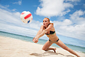 'A girl in a two piece bathing suit playing beach volleyball; Waikiki, Hawaii, United States of America'