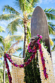 'Statue of a man covered in floral leis standing against a surfboard; Honolulu, Oahu, Hawaii, United States of America'