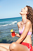'A young woman in a bikini holds a drink and laughs while sitting at the water's edge; Honolulu, Oahu, Hawaii, United States of America'