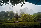 'Lush Foliage And Mountain Peaks On A Rainy Day; Yangshuo, China'