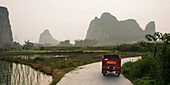 'A Truck Travels Down A Road At Sunset Beside Peaked Mountains And Water; Yangshuo, Guangxi Province, China'