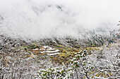 'An Ancient Tibetan Buddhist Temple Between Two Snowy Mountain Slopes In The Mist; Huanglong, Sichuan Province, China'