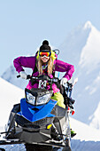 Lynsey Dyer Goofing Around On Her Snowmobile Ready To Do Some Backcountry Skiing In The Chugach Mountains, Late Winter, Southcentral Alaska.