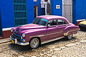 'Bright Purple Chevy Parked In Front Of A Blue Building; Trinadad, Sancti Spiritus, Cuba'