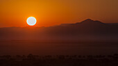 'Sunrise With A Silhouette Of The Landscape; Namibia'