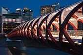 'Red Bridge At Night With Lights And City Buildings In The Background; Calgary, Alberta, Canada'