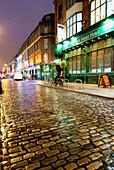 'Wet Street And Lights Illuminating Buildings At Nighttime; Dublin, Ireland'