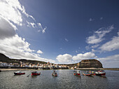 'Boats Mooring In A Row In A Harbour With Houses Along The Waterfront; Staithes, Yorkshire, England'