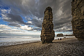'A family walks on the beach along the water with a tall rock column; South Shields, Tyne and Wear, England'