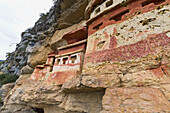 T-shaped windows in the chullpas (stone tomb chambers) of the Chachapoya culture with walls colored with red figures, nestled in the limestone cliffs of Cerro Carbón overlooking the Utcubamba River, Revash, Amazonas, Peru