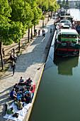 Relaxed atmosphere and strolling on the banks of la villette lake in spring, canal de l'äôourcq, 19th arrondissement, paris, france