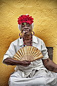 Creole woman smoking a puro cigar posing for the photo with her fan, street scene, daily life, havana vieja, cuba