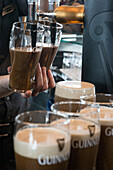 Serving dark draught ale at the old brewery, guinness storehouse, dublin, ireland