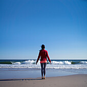 Woman in Casual Clothes Standing on Tiptoes on Beach, Rear View