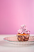 Cupcake with Icing on Dish Against Pink Background
