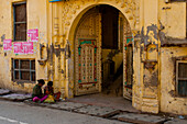 Two young women sits on the street's ground outside of a fancy entrance of a building in India