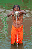 Man with an orange tunic holds a metal can throwing water in the holy Ganges river with a green background reflecting in the water, Varanasi, India