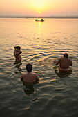 Three devotees wash in the Ganges river waters while a boat passes and the sun is rising in the background