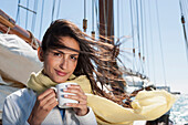 Caucasian woman drinking coffee on sailboat, Cape Town, Western Cape, South Africa