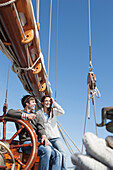 Caucasian couple at helm of sailboat, Cape Town, Western Cape, South Africa