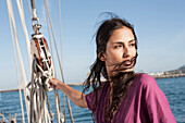 Caucasian woman hoisting sail on sailboat, Cape Town, Western Cape, South Africa