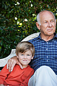 Caucasian boy sitting with grandfather on bench, Cape Town, Western Cape, South Africa