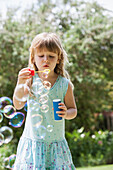 Caucasian girl blowing bubbles outdoors, Cape Town, Western Cape, South Africa